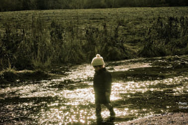 Kid walking on a river bank