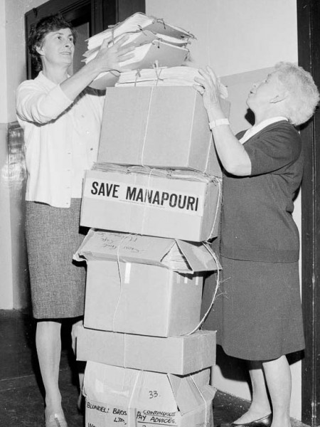 "Two female Forest & Bird staff help to stack a 1.5 metre tall pile of boxes containing petitions for the ""Save Manapouri"" campaign."