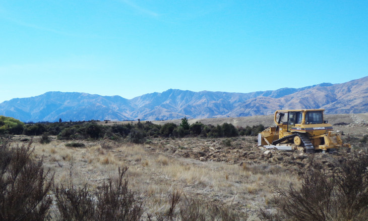 Otago Hawea river terraces being cleared by a bulldozer of mixed kanuka grey shrubland and grassland cushion field ecosystem
