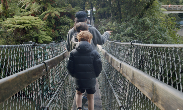 Family cross a swing bridge