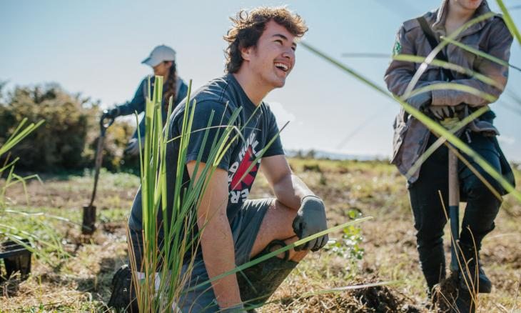 Young man smiling while planting a cabbage tree outside.